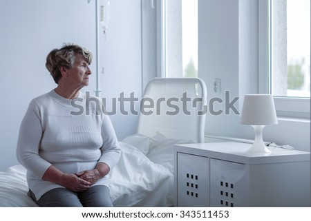 Ill lonely woman sitting on hospital bed - stock photo