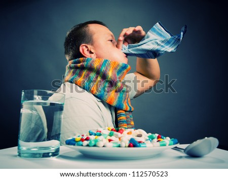 Ill man blowing his nose - stock photo