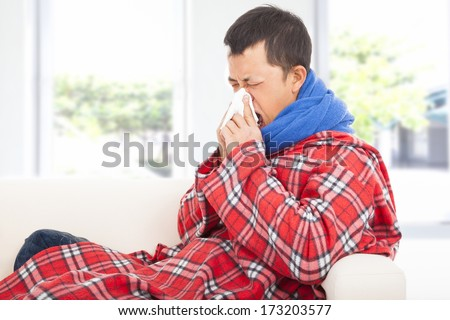 ill man blowing nose with tissue on sofa at home - stock photo