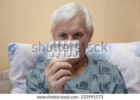 Ill senior man looking at pills. - stock photo
