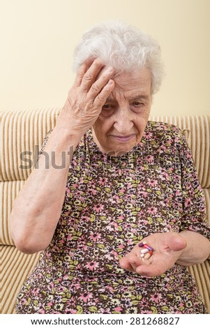 ill senior woman holding pills on palm - stock photo