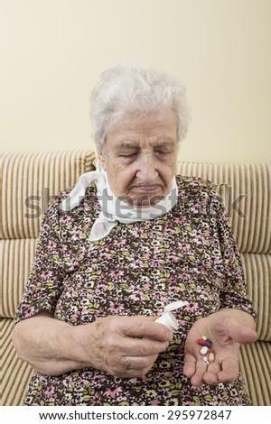 ill senior woman taking pills - stock photo