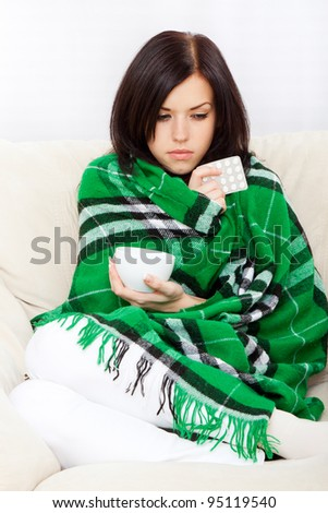 Ill woman covered with blanket holding cup of tea and pack of pills, sitting at home on sofa couch - stock photo