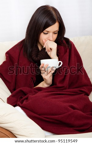 Ill woman covered with blanket holding cup of tea, sitting at home on sofa couch - stock photo