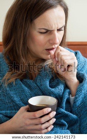 Ill woman in bed drinking tea, vertical - stock photo