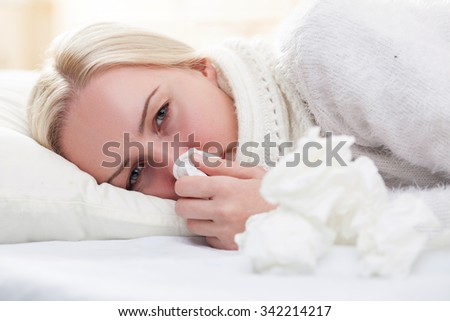 Ill young blond woman is lying in bed with frustration. She has a flue and fever. The lady is blowing into the napkin - stock photo
