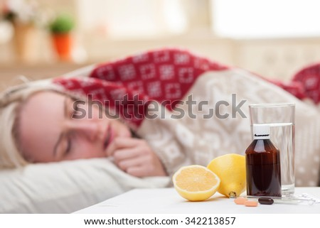 Ill young woman is sleeping in bed. She has a fever. Focus on pills, lemon and a glass of water on the table - stock photo