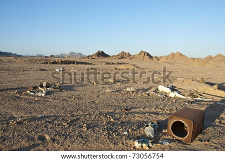 Illegal waste dump in the desert, mountains in the background against a blue sky. South Sinai, Egypt. - stock photo