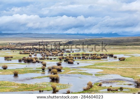 Illinois River meanders through Arapaho National Wildlife Refuge, North Park near Walden, Colorado, spring scenery with flooded meadows - stock photo