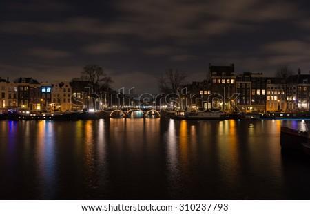 illuminated amsterdam canal and bridge at night - stock photo