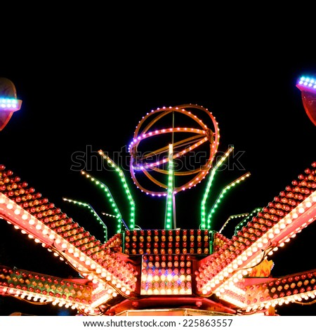 Illuminated amusement park at night - stock photo