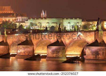 Illuminated arches of the Charles bridge across Vltava river in autumn evening, Prague, Czech Republic - stock photo