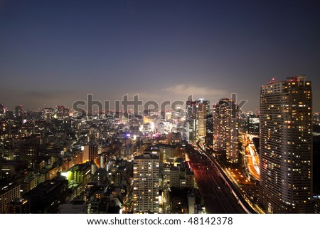 Illuminated buildings and roads of night skyline in Tokyo during sunset - stock photo