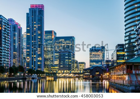 Illuminated buildings in Canary Wharf, financial hub in London at evening - stock photo