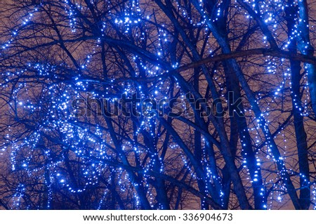 Illuminated Christmas or New Year light garlands on trees at night - stock photo