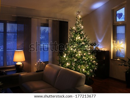 Illuminated Christmas tree decorated in modern living room - stock photo
