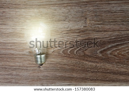 Illuminated common  light bulb laying on wooden board - stock photo