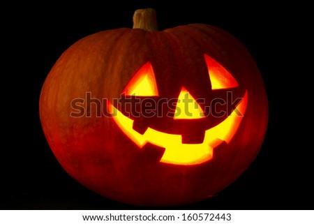 Illuminated cute halloween pumpkin on black background - stock photo