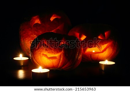 Illuminated cute halloween pumpkins and candles isolated on black background - stock photo
