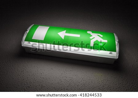 Illuminated emergency exit sign mounted on the wall in dark room - stock photo