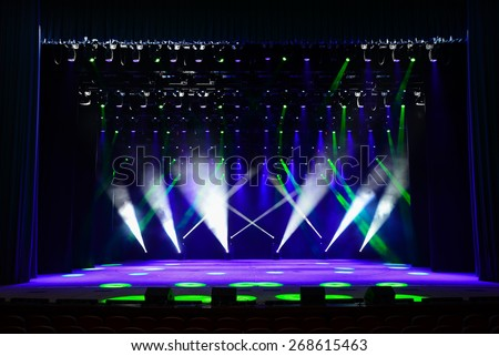 Illuminated empty theater stage with fog and rays of light - stock photo