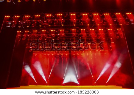 Illuminated empty theater stage with smoke - stock photo
