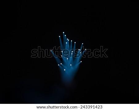 illuminated fiber optic threads  on black background - stock photo