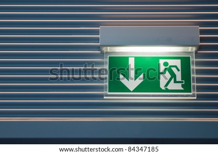 illuminated green emergency exit sign on a modern wall - stock photo