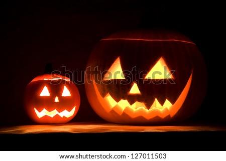 illuminated halloween pumpkins by night - stock photo