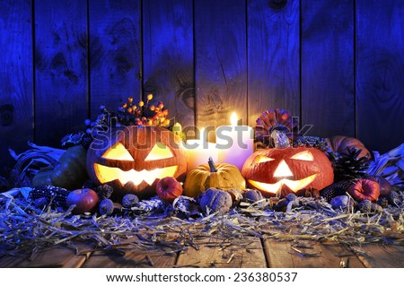 illuminated halloween pumpkins, candles, nuts, maize-cob and apple on straw in front of old weathered wooden board in blue light - stock photo