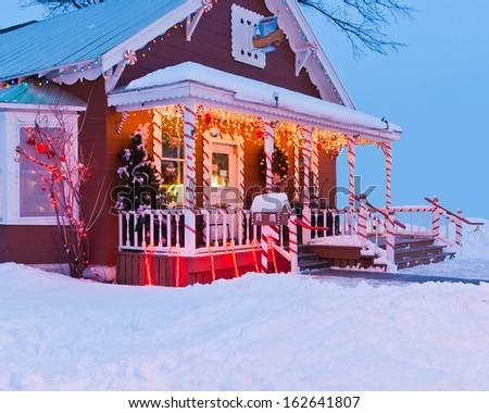 Illuminated house with Christmas decoration - stock photo
