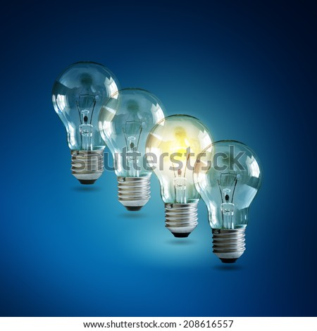 Illuminated light bulb in a row of dim ones concept for creativity, innovation and solution - stock photo