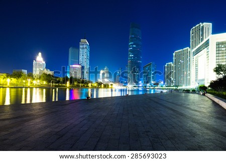 Illuminated modern skyscrapers and skyline at riverbank. - stock photo