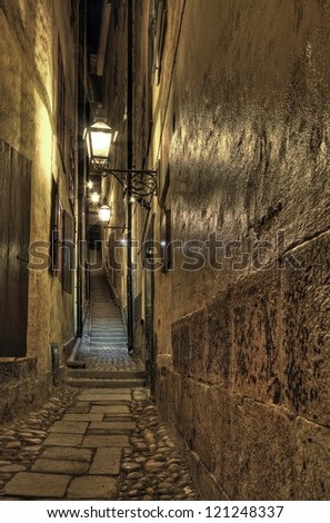 Illuminated narrow alley at night in Stockholm Old Town. - stock photo