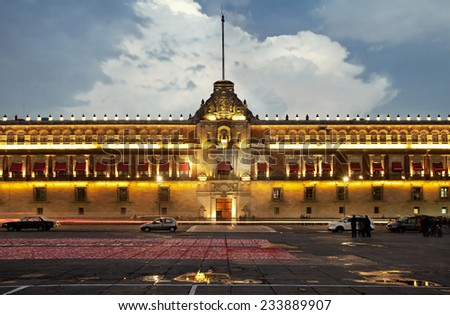 Illuminated National Palace in Plaza de la Constitucion of Mexico City at sunset. Zocalo and Army Square are among other local names of this place. - stock photo