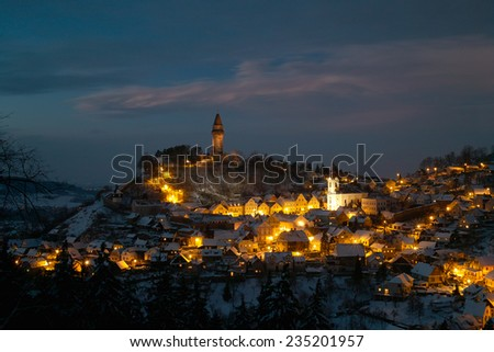 Illuminated old town with castle on snowy Christmas evening - stock photo