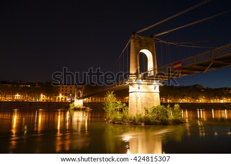 Illuminated Passerelle du College footbridge over the Rhone river in Lyon, France, on a clear evening. - stock photo