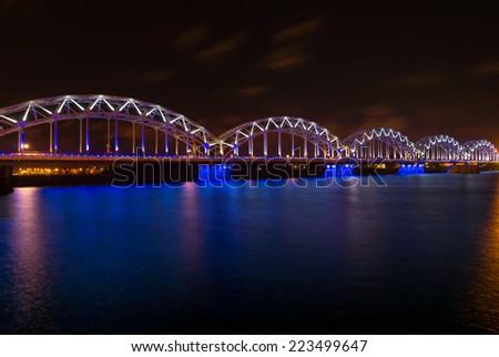 Illuminated railway bridge at night in Riga, Latvia - stock photo
