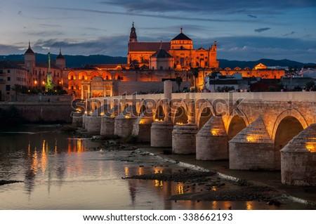 illuminated Roman bridge and La Mezquita at sunset in Cordoba, Andalusia, Spain. Guadalquivir river - stock photo