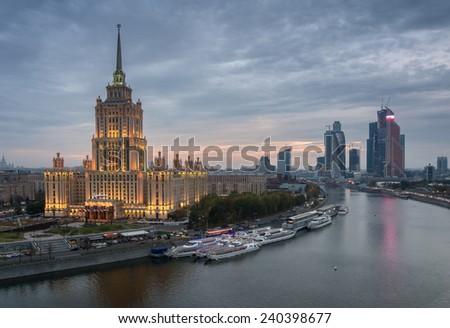 Illuminated Royal Hotel Radisson (Hotel Ukraina) near river at evening.  - stock photo