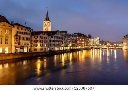 Illuminated Saint Peter Church and Houses along Limmat River Bank in the Evening, Zurich, Switzerland - stock photo