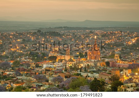 Illuminated skyline of San Miguel de Allende in Mexico after sunset, with a yellow filter effect. - stock photo