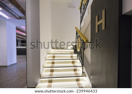 Illuminated stairs in empty corridor - stock photo
