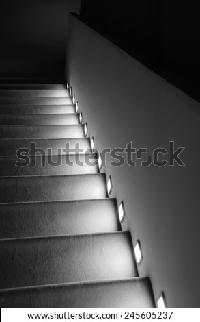 Illuminated stairs in the building. Suspense background. Black and white. - stock photo