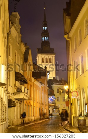 illuminated street in old part of tallinn by night. St. Olafs church - stock photo
