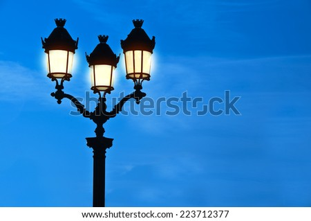 Illuminated street light at night, blue sky background, Paris, France - stock photo