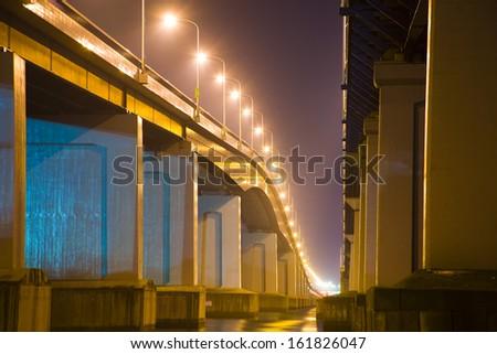 Illuminated street lights on bridge at night - stock photo