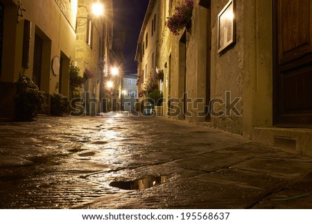 Illuminated Street of Pienza after rain at Night, Italy - stock photo