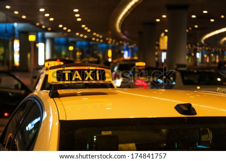 illuminated taxi sign on a taxi roof at night - stock photo