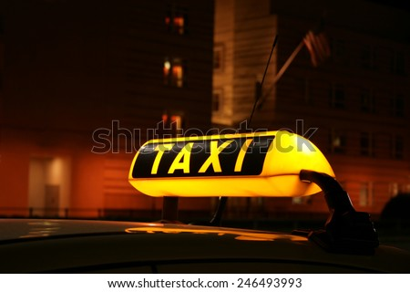 Illuminated TAXI sign on car cab waiting for a fare in the city at night, seen in front of the Berlin US Embassy - stock photo